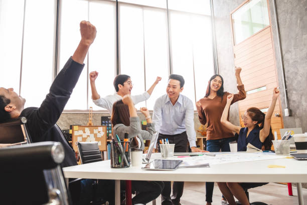 Business people smile and raise hands up, feeling happy, complete finish job, teamwork successful/achievement working in office concept stock photo