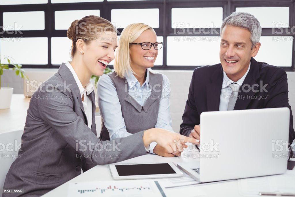 Business people smiling while discussing over laptop royalty-free stock photo