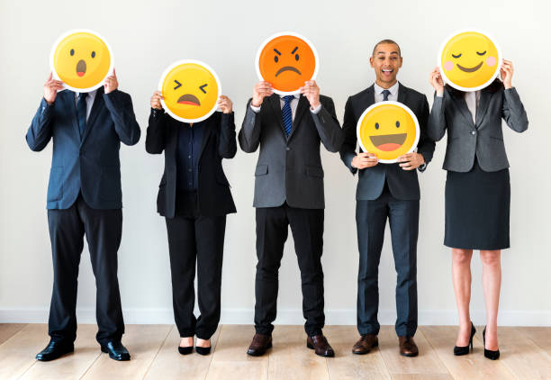business people standing and holding emoji icons - emoji foto e immagini stock