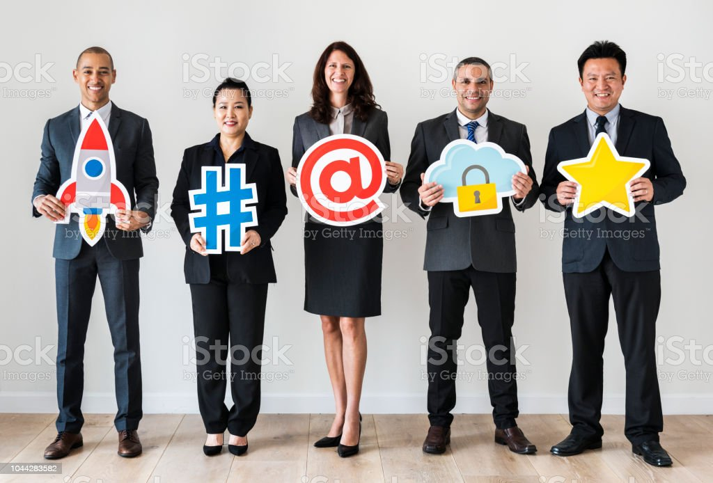 Business people standing and holding icons stock photo