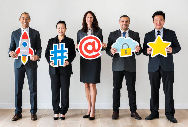 business people standing and holding icons - rocket logo stock photos and pictures