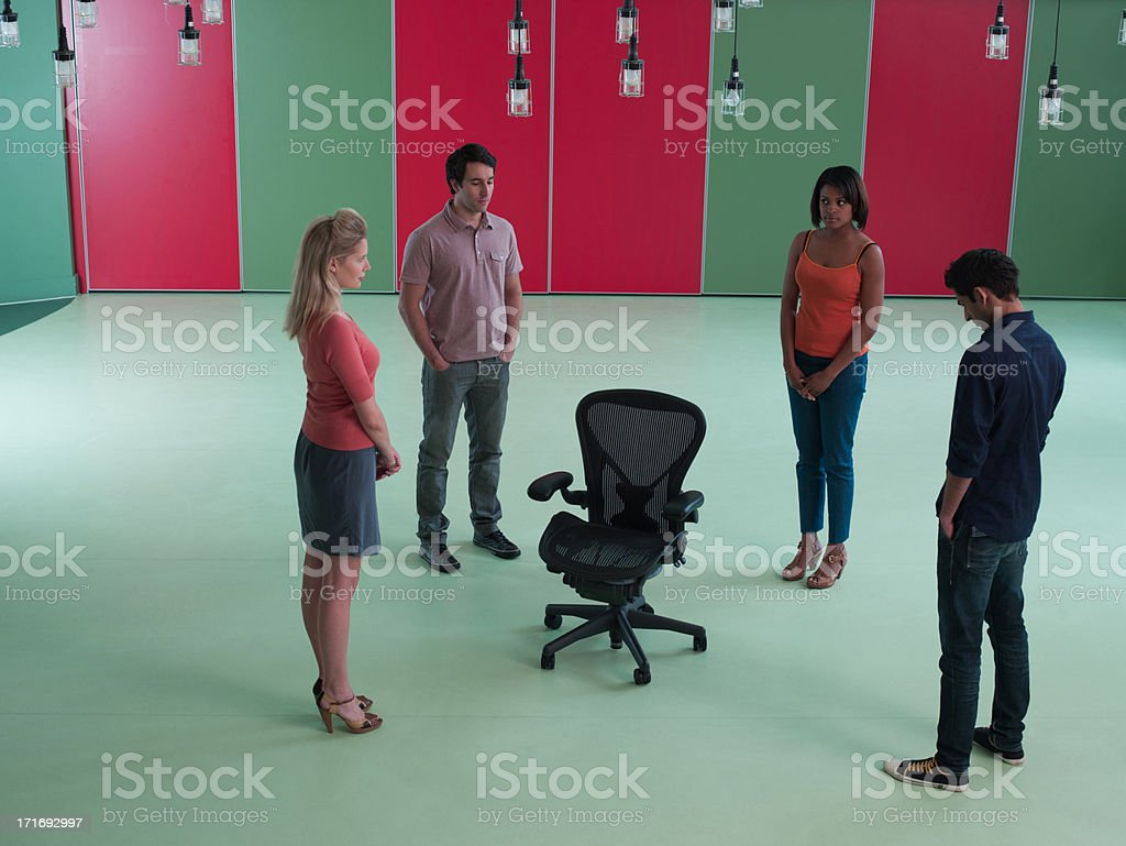 Business people standing around empty chair stock photo