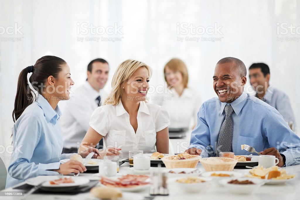 Business people standing around table at lunch stock photo