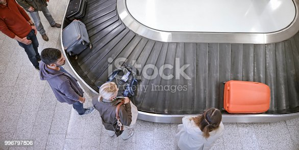 Elevated view of business people standing at baggage claim in airport.
