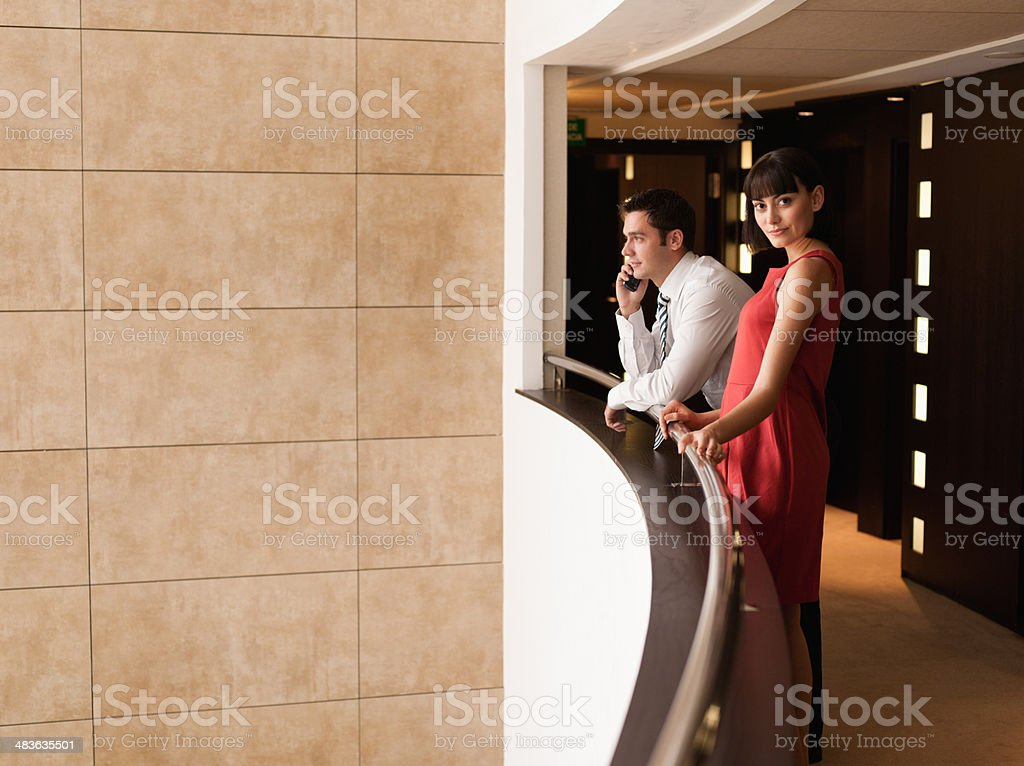 Business people standing at balcony in hotel corridor stock photo