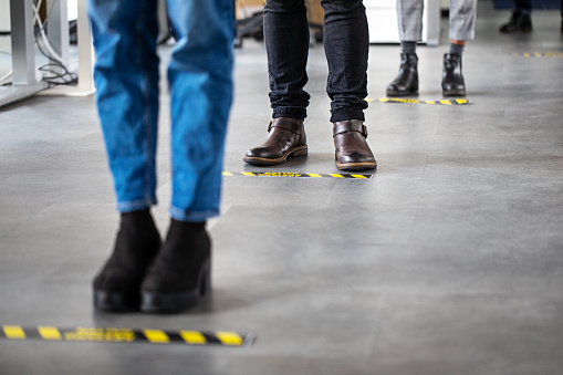 Low angle shot of business people standing behind social distancing signage on office floor. People in queue at office for safe entry checks post corona virus pandemic.