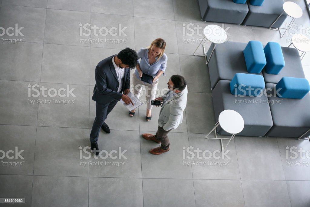 Business people standing in business building and having...