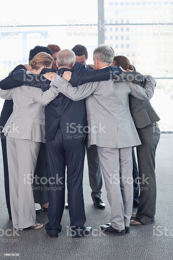 Business people standing in huddle stock photo