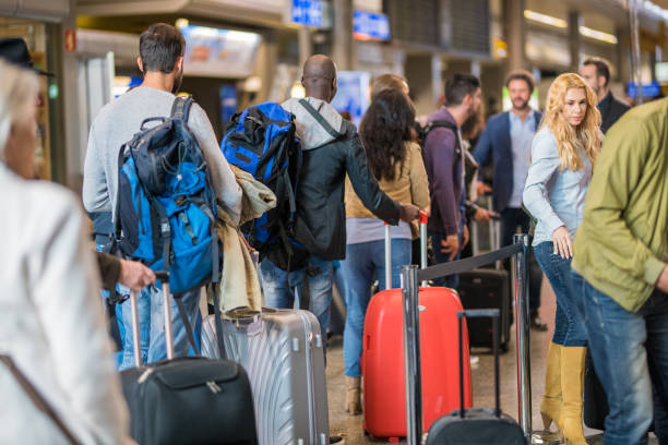 Business people standing in queue at airport Business people standing with luggage in queue at airport arrival area. long hair stock pictures, royalty-free photos & images