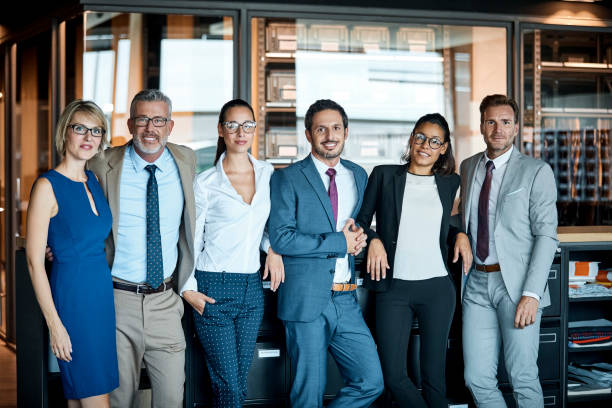 Business people standing in row at textile factory stock photo