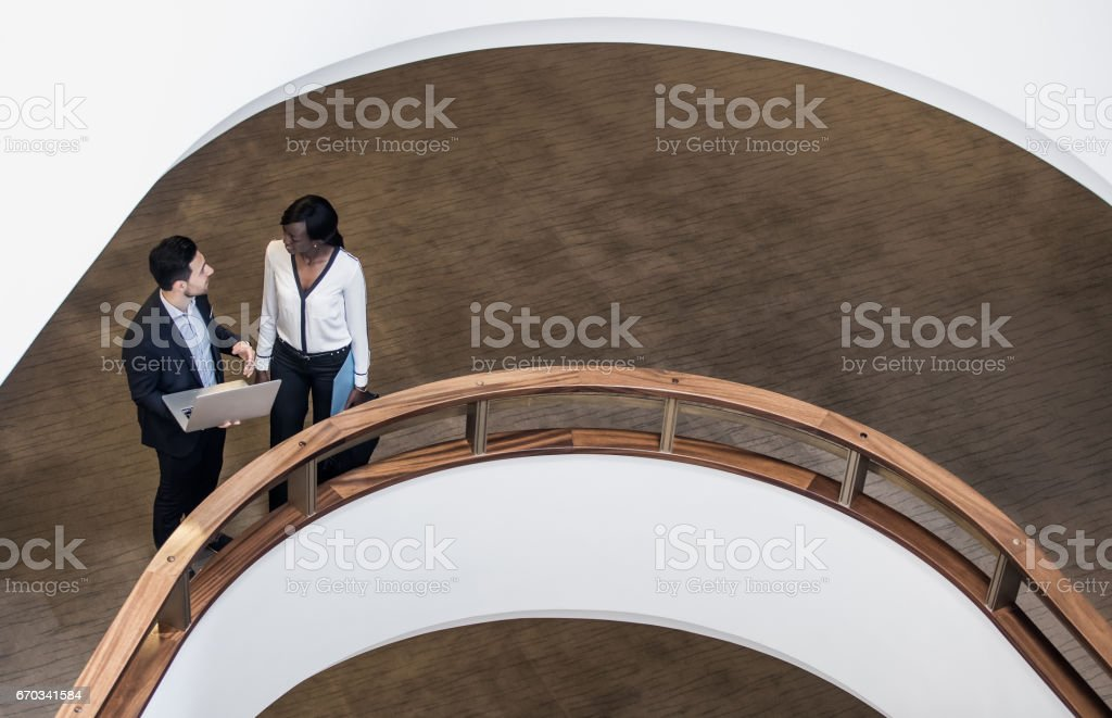 Business People Standing in the Middle of a Building's Corridor, Discussing and Using Laptop stock photo