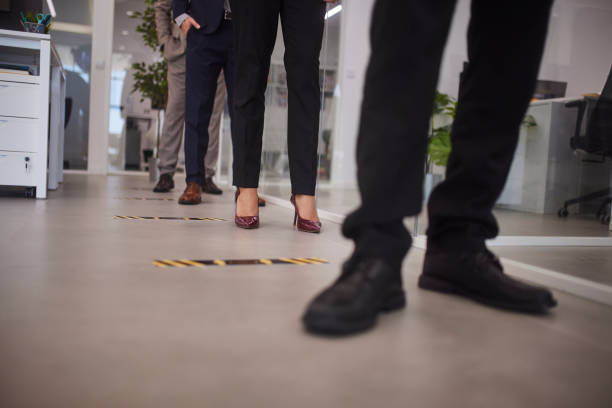Business people standing keeping social distance in office floor stock photo