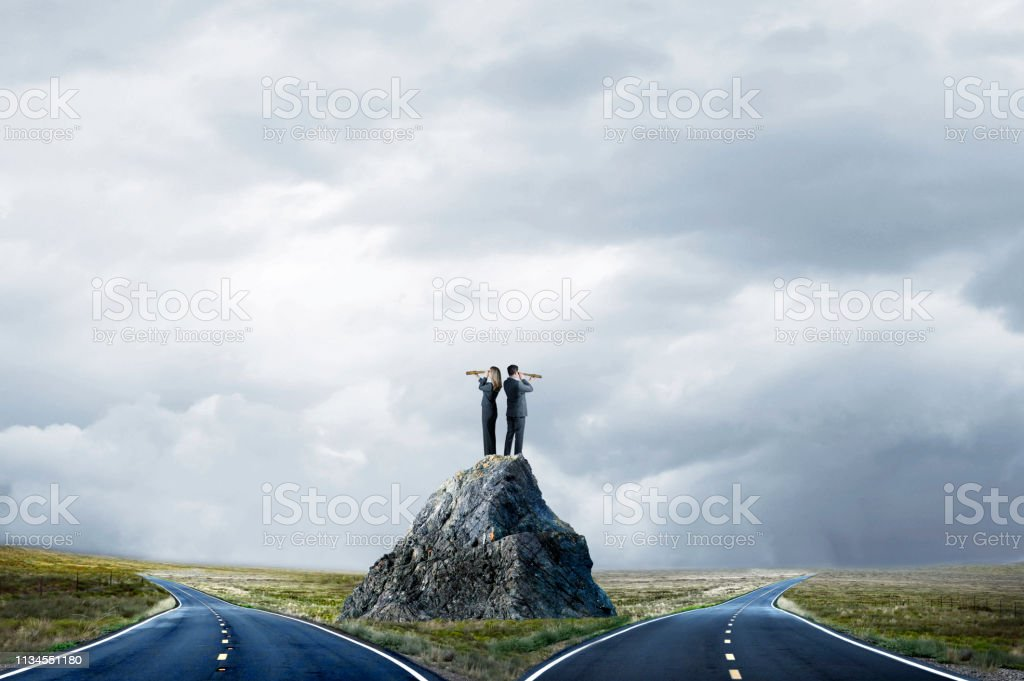 Business People Standing On Large Rock Looking At Fork In The Road stock photo