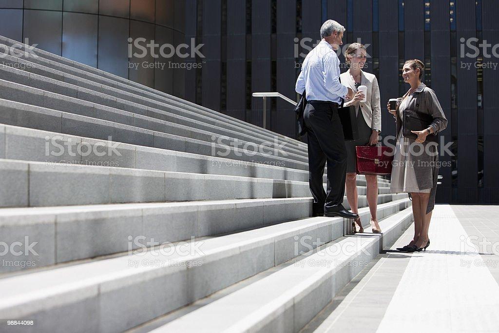 Las personas de negocios de pie en pasos al aire libre foto de stock libre de derechos