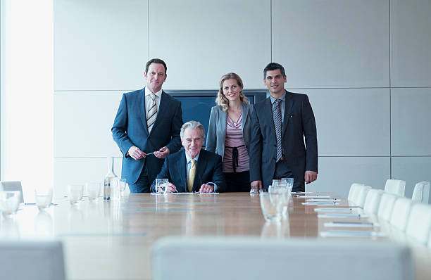 business people standing together in conference room - four people stock photos and pictures
