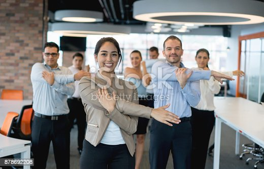 istock Business people stretching at the office 878692208