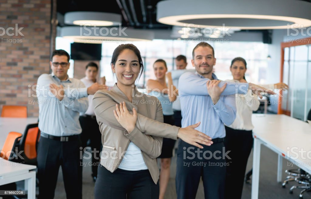 Business people stretching at the office stock photo