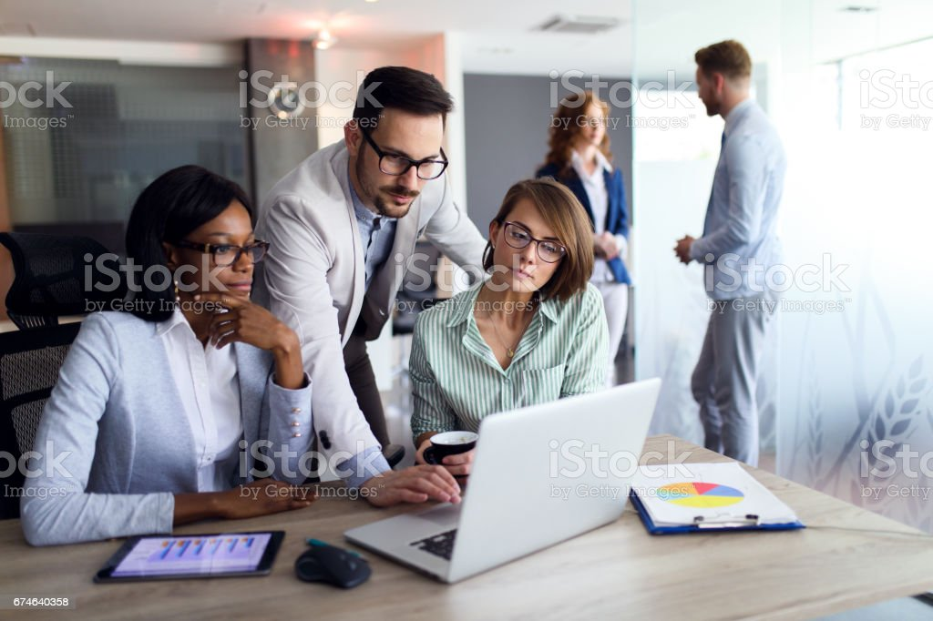 Business people studying statistic report using laptop stock photo