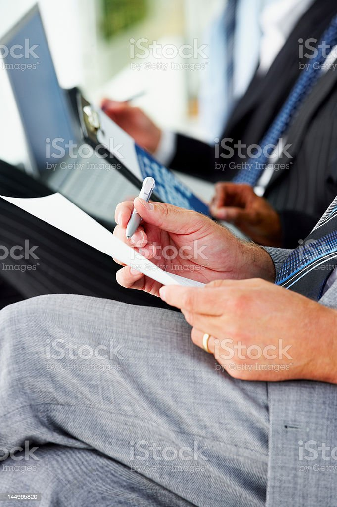 Business people taking notes at a conference royalty-free stock photo