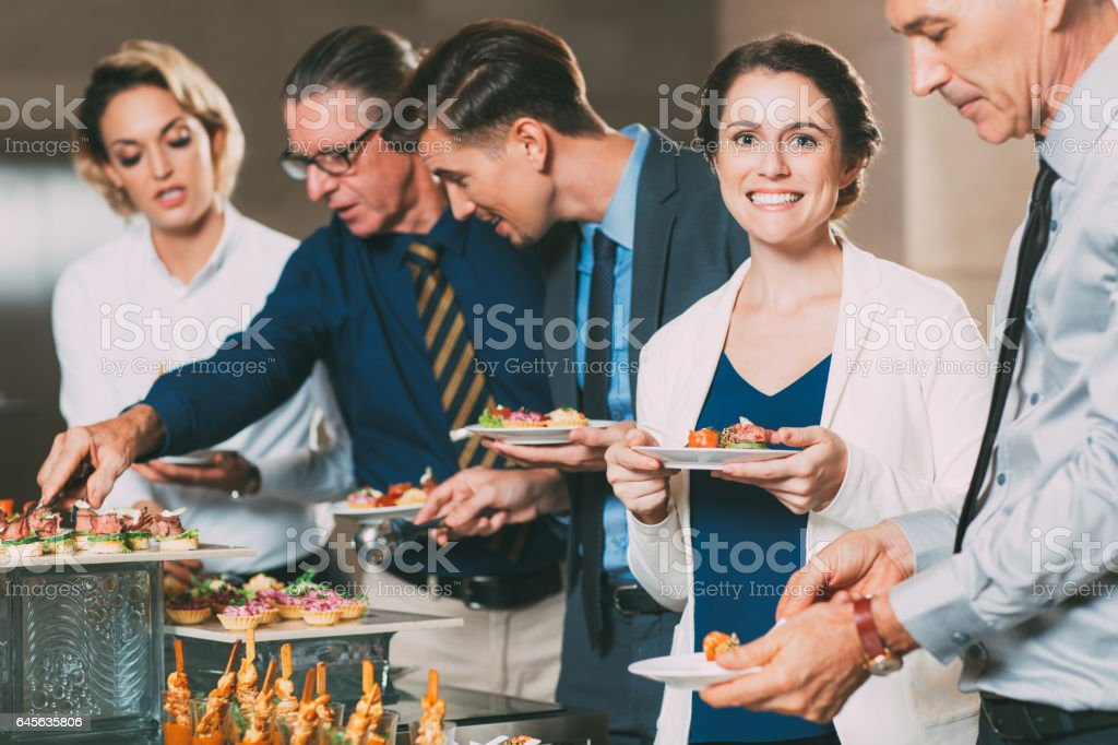 Business People Taking Snacks from Buffet Table stock photo