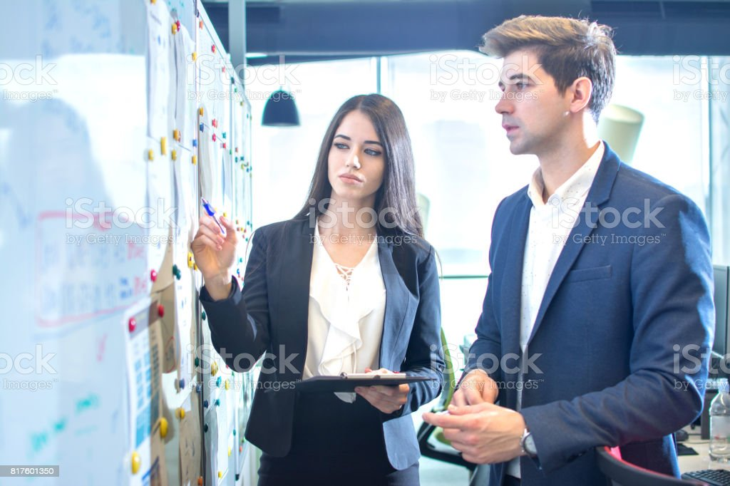 Business people talking and pointing something on a white board in the office. stock photo