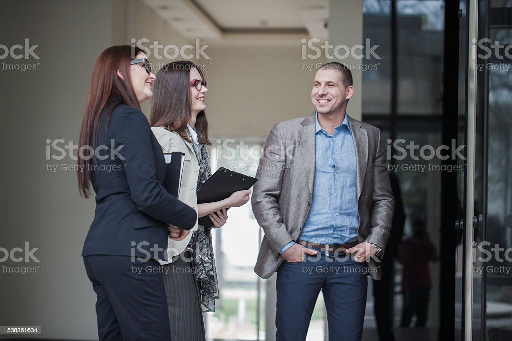 people talking in elevator. business people talking and smiling while waiting for elevator stock photo in r