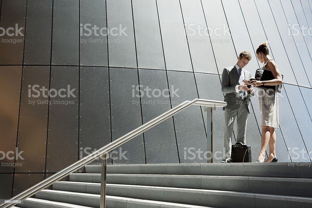 Business people talking at top of steps outdoors stock photo