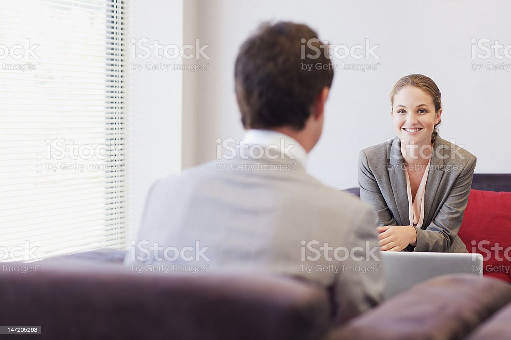Business people talking face to face in lobby stock photo