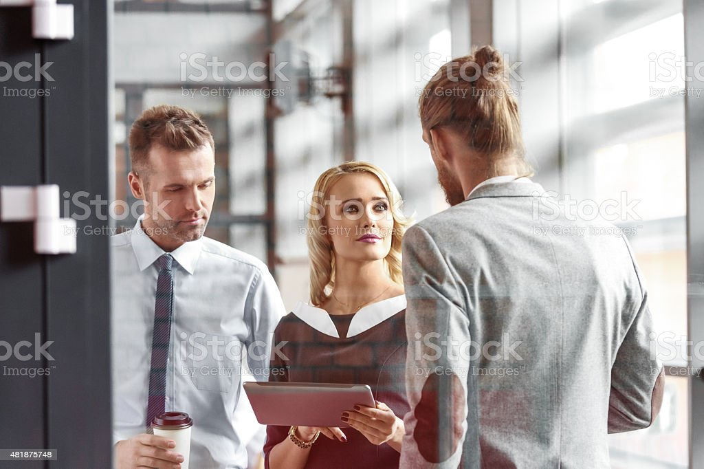 Business people talking in an office, woman holding digital tablet Businesswoman and two businessmen discussing in an office. Woman holding digital tablet in hands. Photo taken through glass. 2015 Stock Photo