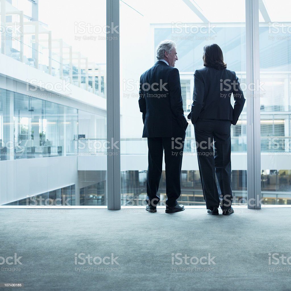 Business people talking near glass wall in office stock photo