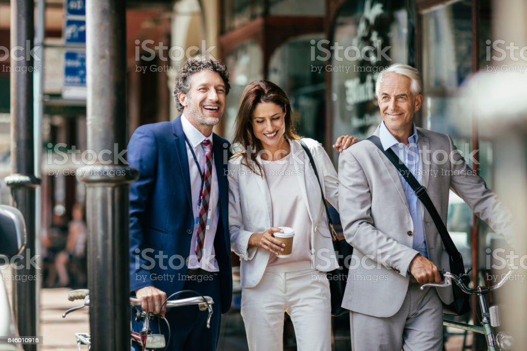 Close up of business people talking on the street while having...