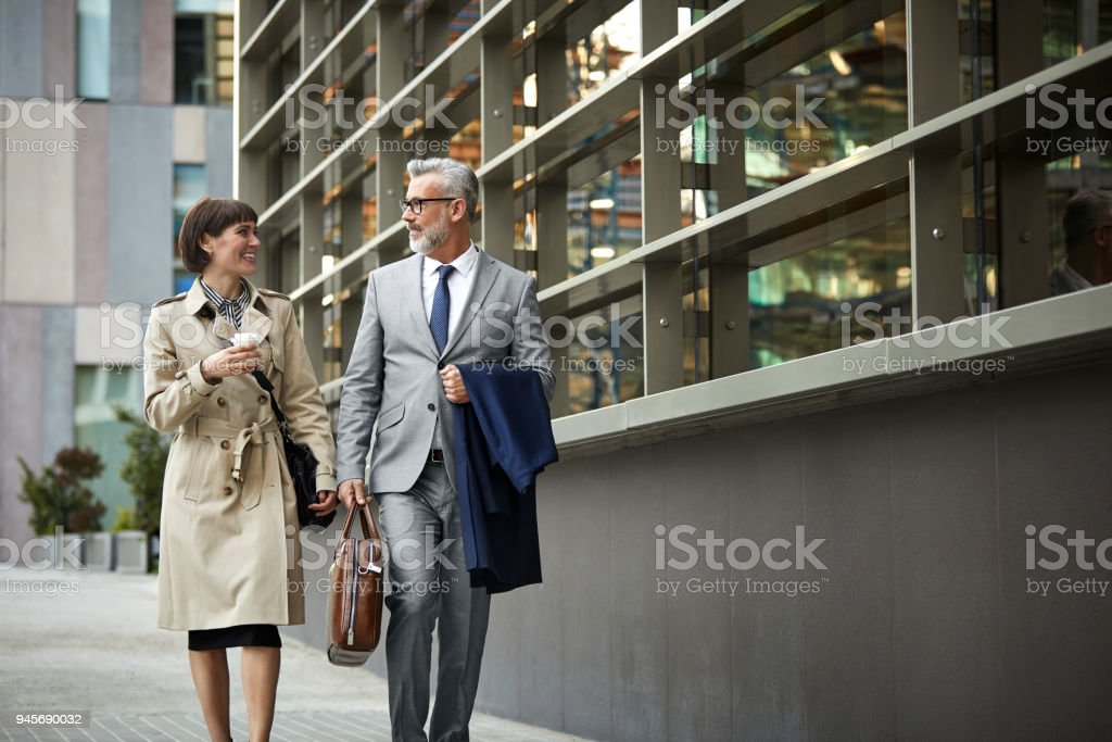 Businesswoman and businessman walking on street. Male and female...