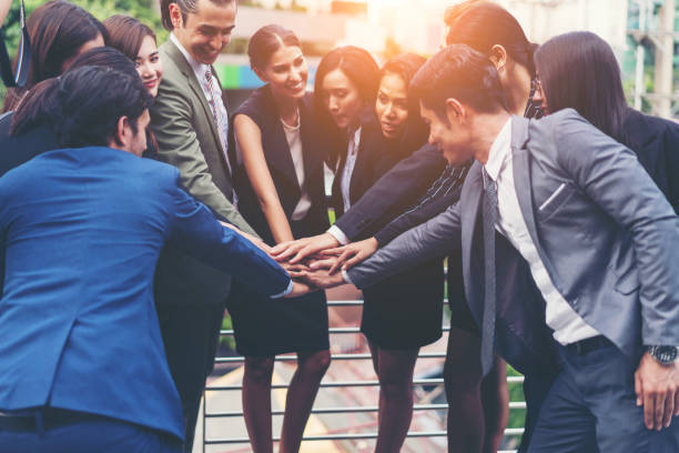 Business people team meeting and putting hands together at outdoors. Friends with stack of hands showing unity and teamwork. Concept of team success, people creative, business goal and power of group. stock photo