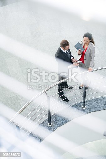 High angle  conceptual portrait of two business people, man and woman, standing by rail at balcony of modern office building and discussing work, copy space