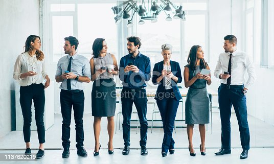 Young successful Business people using digital devices standing in a row