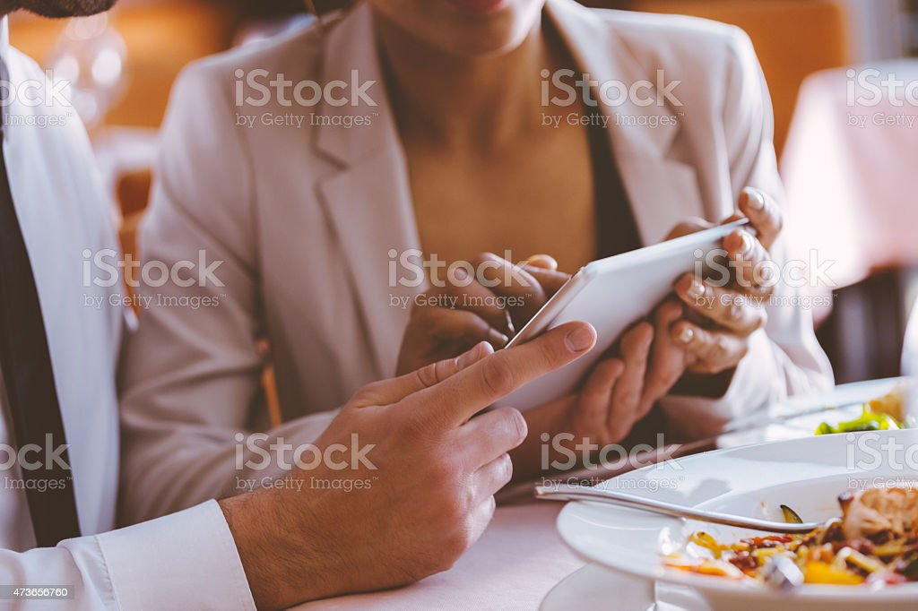 Business people using digital tablet at lunch Businesswoman and businessman having lunch or dinner in the restaurant, using digital tablet together. Close up of hands. Plates on the table. Unrecognizable person. 2015 Stock Photo