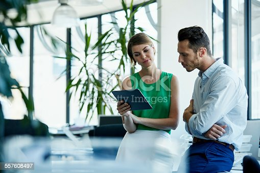 557608497istockphoto Business people using digital tablet in office 557608497