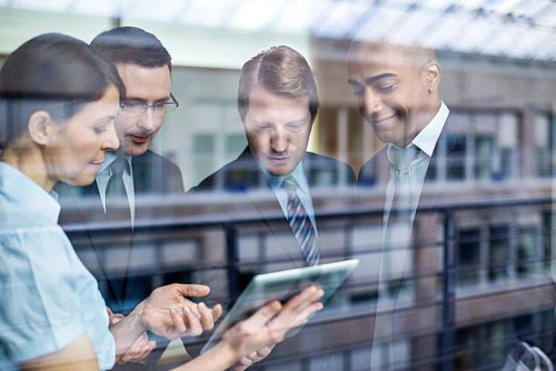 geschäftsleute mit digitalen tablet im büro - alvarez stock-fotos und bilder
