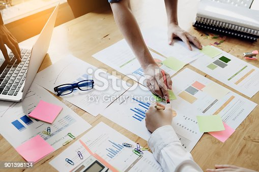 881542122istockphoto Business people using pen pointing graph chart paper of conference and use laptop computer for income & budget of sale in this year. 901398134