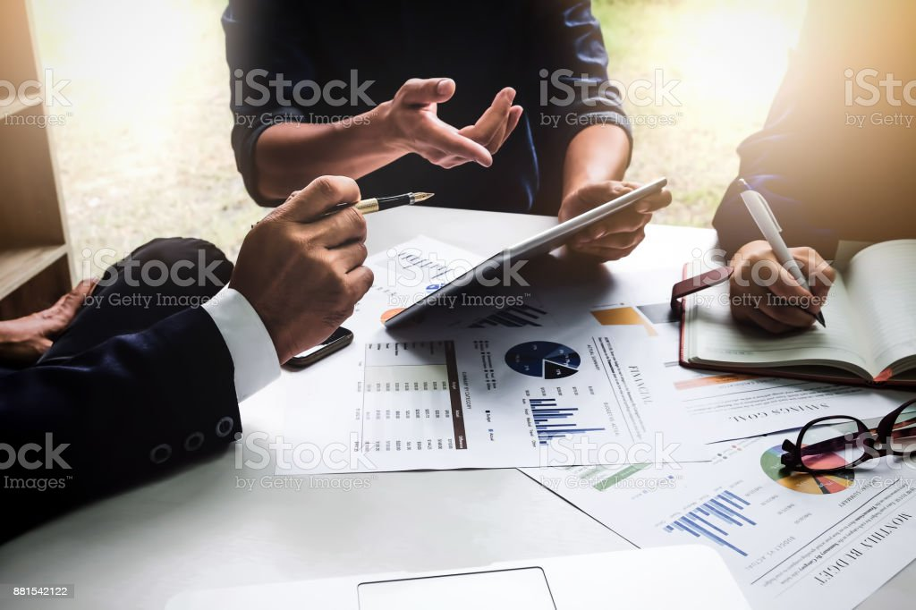 Business people using pen,tablet,notebook are planning a marketing plan to improve the quality of their sales in the future. stock photo