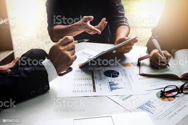 Business people using pen,tablet,notebook are planning a marketing plan to improve the quality of their sales in the future.