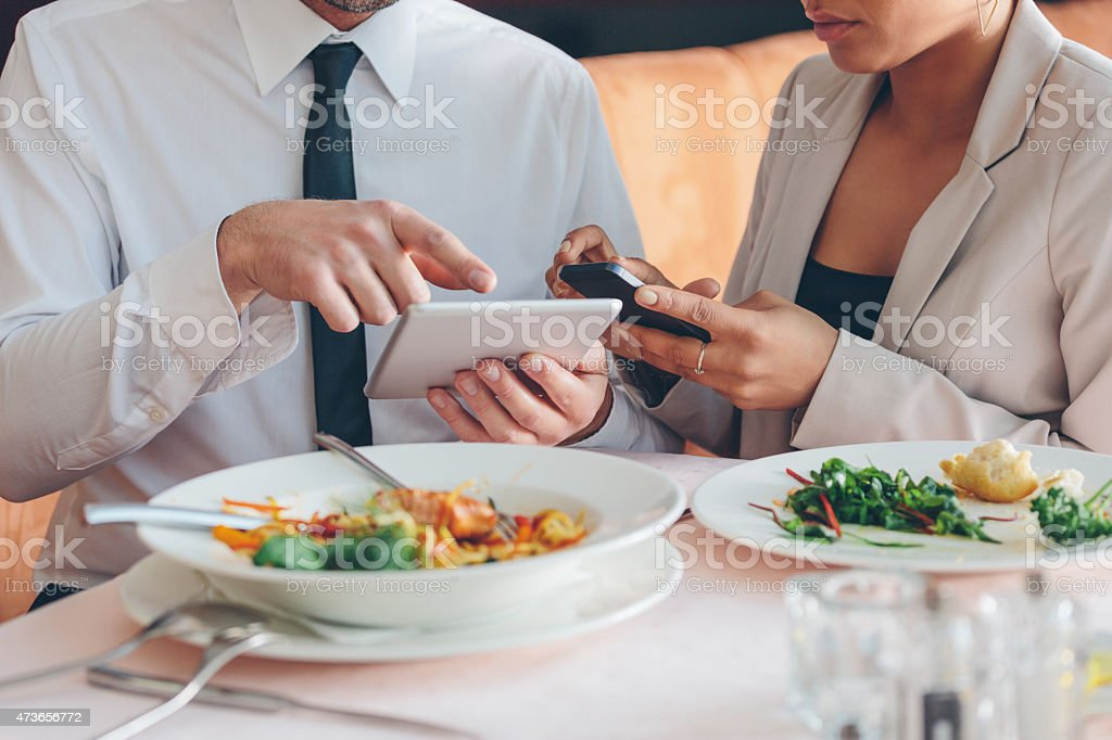 Business people using smart phone and digital tablet at lunch Businesswoman and businessman having lunch or dinner in the restaurant, man using digital tablet and woman using smart phone. Close up of hands. Plates on the table. Unrecognizable person. 2015 Stock Photo
