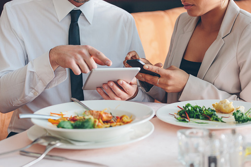 Business People Using Smart Phone And Digital Tablet At Lunch Stock Photo - Download Image Now