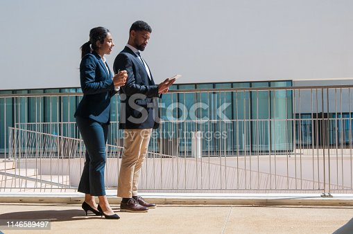 Business people using tablet and standing outdoors. Business man and woman wearing formal clothes with building in background. Business people and technology concept. Side view.