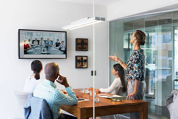 Business people video conferencing in board room stock photo