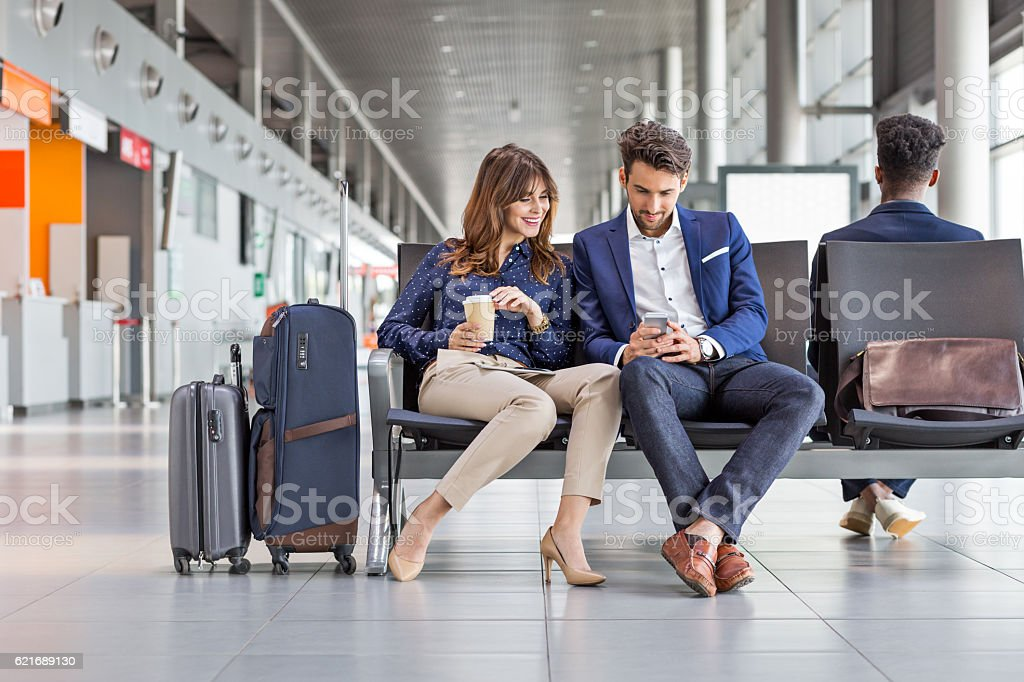 Business people waiting for flight at airport lounge stock photo