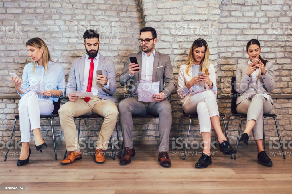 Business people waiting for job interview. They use their phones...