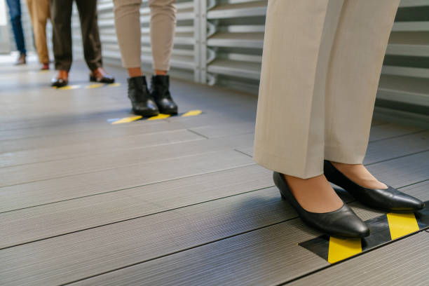 Business people waiting in line behind social distancing sign on floor stock photo