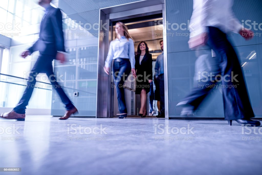 Business people walk out of the lift in the lobby. stock photo