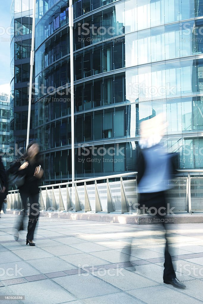 Business people walking along office building, blurred motion royalty-free stock photo